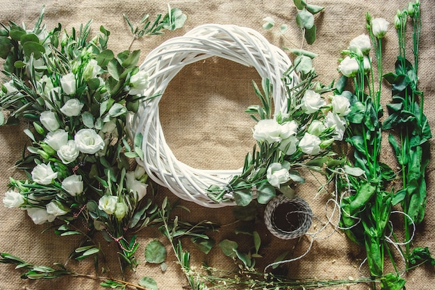 Венок с белыми розами на фоне джута. украшен