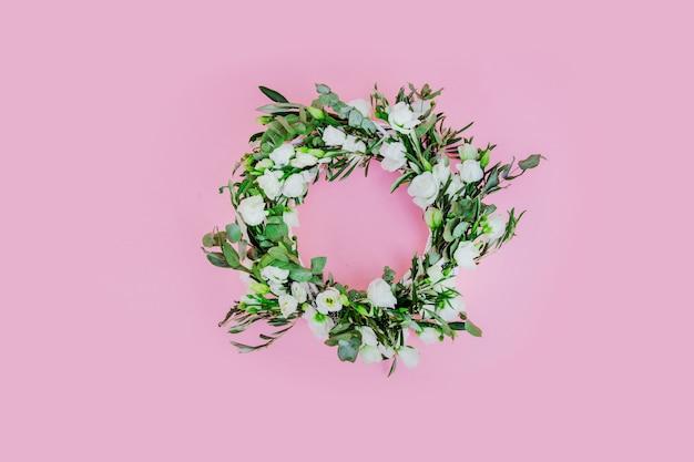 ピンクの背景に白いバラと花輪。飾られた。上図