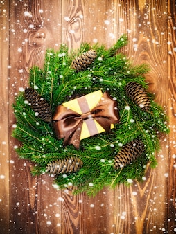 Wreath on the wooden board. wrapped gift box. christmas