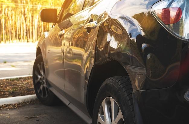 도로에서 사고 후 난파된 검은 차. 주차장에 깨진된 자동차