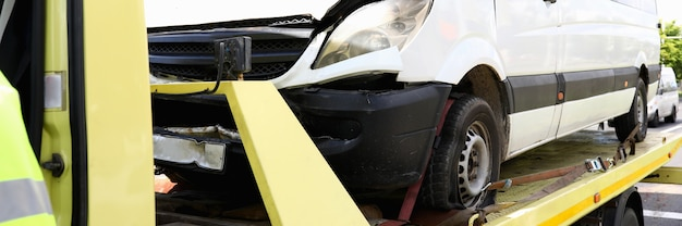 破壊された車はレッカー車のクローズアップの上に立っています。車の避難サービスの概念