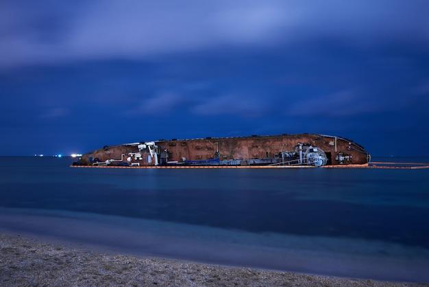 Разбитый корабль танкера в тихом море ночью.