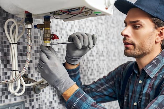 항상 작업자와 함께 렌치가 가정 욕실에 전기 난방 보일러를 설치합니다.