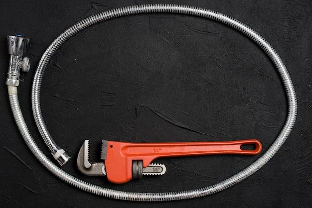 Гаечный ключ и гибкий разъем на темном столе