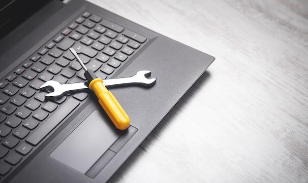 Гаечный ключ и отвертка на клавиатуре компьютера.