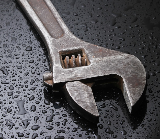 Wrench on black with water drops.
