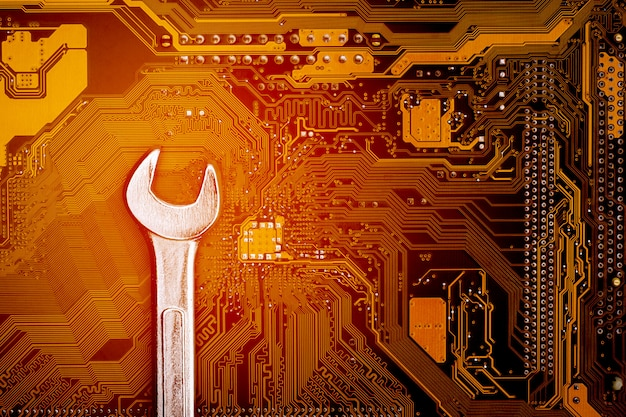 Wrench on computer circuit board. - maintenance and security computer concept.