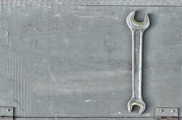 灰色の塗装された木の表面にレンチを掛けます。手作業用の金属工具