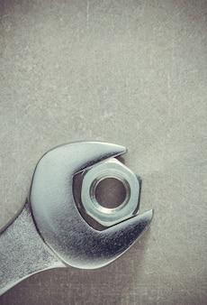 렌치 도구와 너트 금속 배경