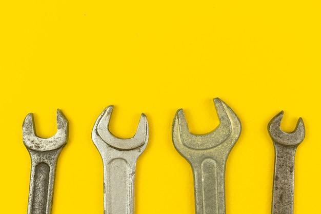 노란색 사무실 테이블 배경이 있는 렌치 도구 작업자 테두리 구성, 평면 레이아웃 및 복사 공간이 있는 위쪽 보기 사진