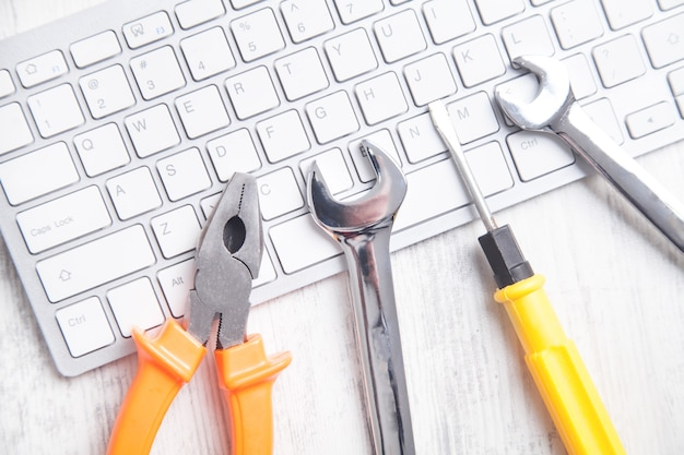 Wrenches on the computer keyboard. it service. support
