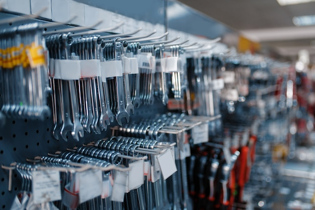 Wrenches on racks in tool store closeup, nobody. choice of equipment in hardware shop, professional instrument in supermarket