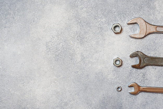 Wrenches, tools bolts and nuts on grey concrete background with copy space.