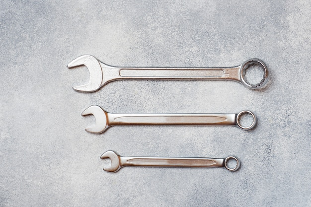Wrenches, tools on gray concrete background with copy space.