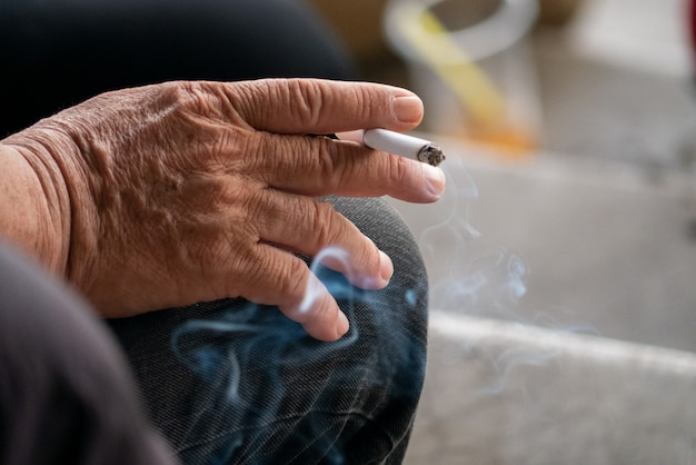 Wrinkle hand hold cigarette with smoke for stop smoking and anti cancer concept