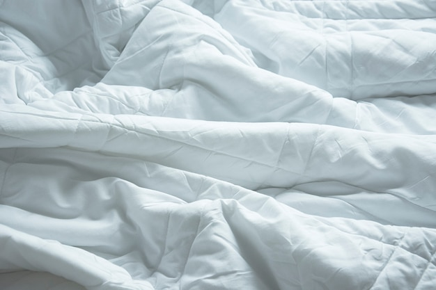朝の目覚めの後の寝室のしわ乱雑な毛布。長い夜の睡眠から、羽毛布団と毛布の詳細、白い毛布を備えたホテルの寝室の整えられていないベッド。