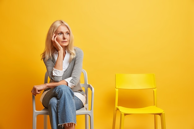 Wrinkled blonde european woman being deep in thoughts sits on comfortable chair waits for something feels lonely and melancholic wears stylish clothes