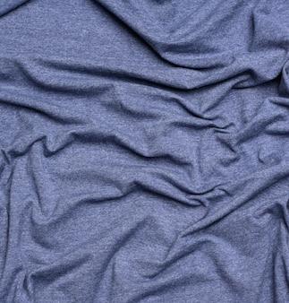 티셔츠와 의류를 바느질하기위한 주름진 블루 코튼 원단을 닫습니다.