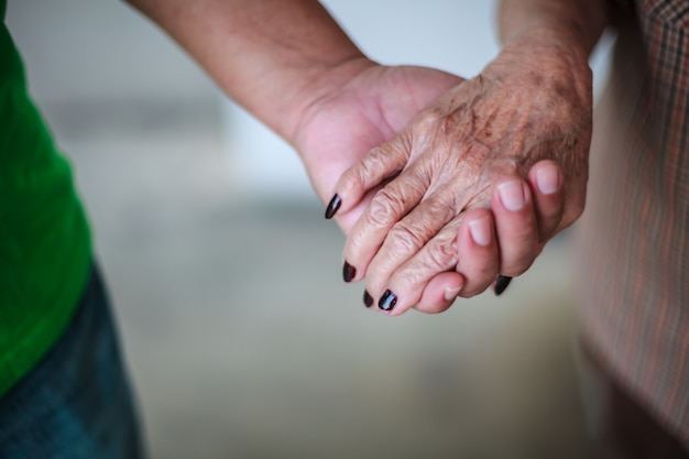 Wrinkled elderly woman's hand holding to young man's hand. family relation.