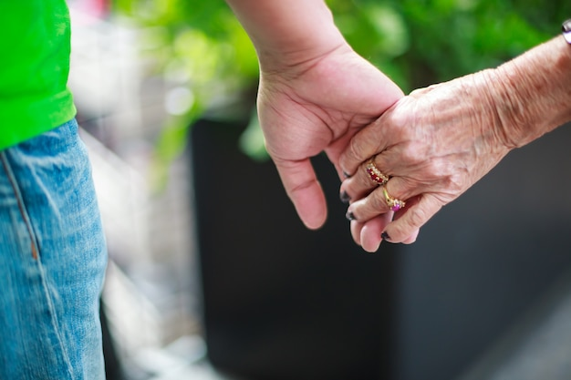 Wrinkled elderly woman's hand holding to young man's hand, walking in park