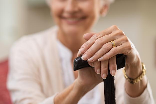 Wrinkled hands holding walking stick
