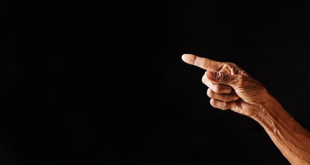 Wrinkled old man hand pointing finger on dark background