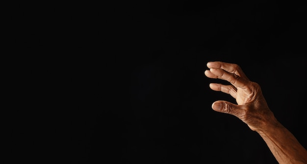 Wrinkled old man's hand with empty hand on dark background