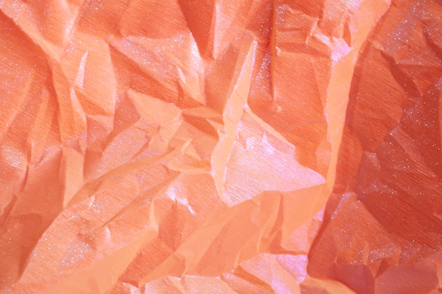 Wrinkled orange holographic crumpled paper abstract background