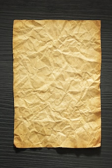 Wrinkled paper at wooden background