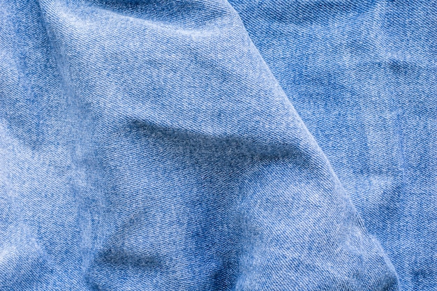 Wrinkles on blue jeans, denim, texture. top view close up.