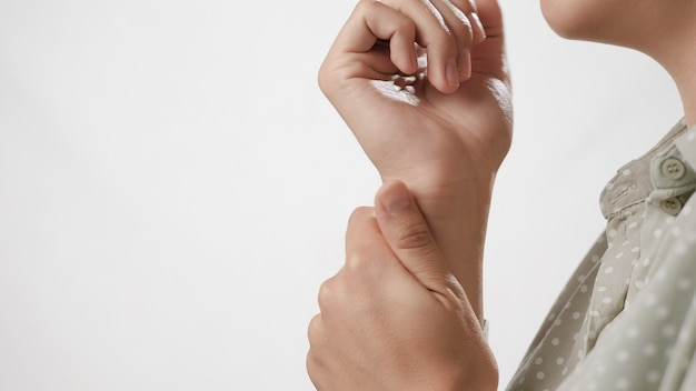 Боль в запястье женская рука касается запястья на белом фоне крупным планом