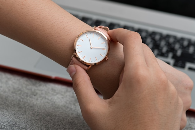 Wrist watch on girl's hand in front of a notebook computer