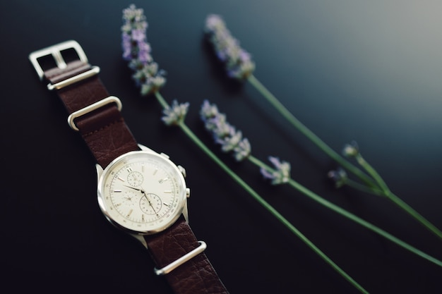 Wrist watch on a leather strap with lavender sprigs on a black background.