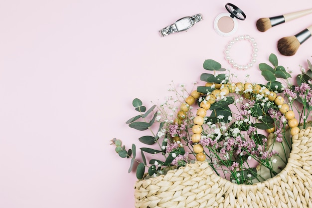 Wrist watch; makeup brush; pearls bracelet; compact face powder with limonium and gypsophila flowers in the wicker bag against pink background