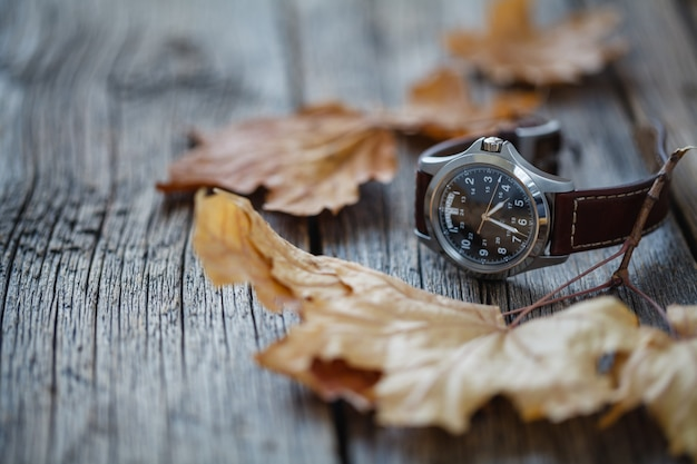 Wrist watch on wooden table with fall leaf