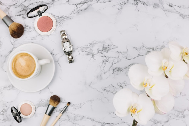 Wristwatch; coffee cup; compact powder; makeup brush and orchid flower on marble background
