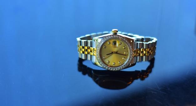 손목시계 반짝이는 유리 바닥에 놓인 명품 시계