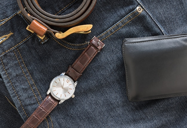 Wristwatch and wallet on denim jeans pocket