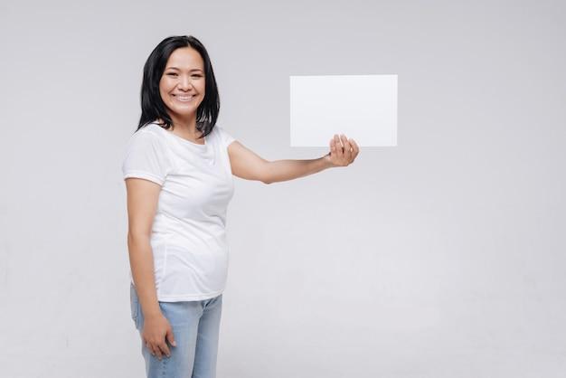 Напишите что-нибудь здесь. вдохновляющая прекрасная сказочная дама держит табличку в руке, стоя и без макияжа