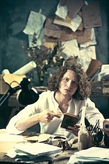 Писатель за работой. красивый молодой писатель сидит за столом и пишет что-то в своем блокноте дома