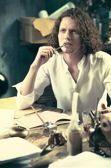 職場でのライター。テーブルに座って、自宅の彼のスケッチパッドで何かを書くハンサムな若い作家
