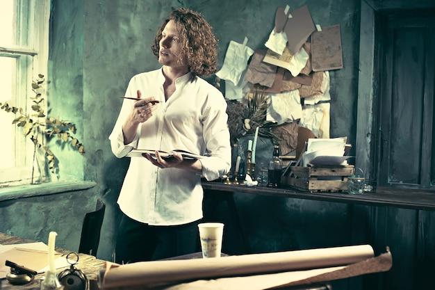 직장에서 작가. 테이블 근처에 서서 집에서 그의 마음에 뭔가를 만드는 잘 생긴 젊은 작가
