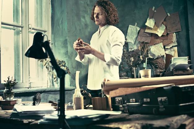 ライター。テーブルの近くに立って、彼の心の中で何かを作るハンサムな若い作家