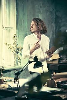 職場でのライター。テーブルの近くに立って、彼の心の中で何かを作るハンサムな若い作家