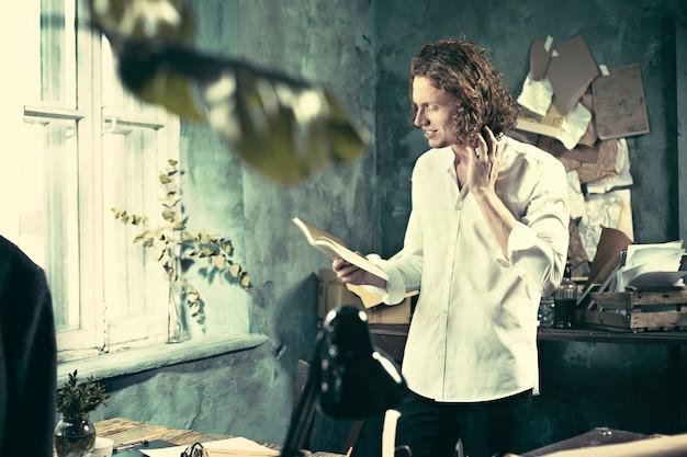 職場の作家。テーブルの近くに立って、彼の心の中で何かを作るハンサムな若い作家
