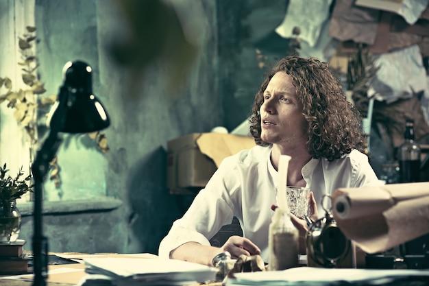 仕事中の作家。テーブルに座って自宅のスケッチパッドに何かを書いている若い作家