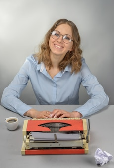 Writer in glasses behind a typewriter