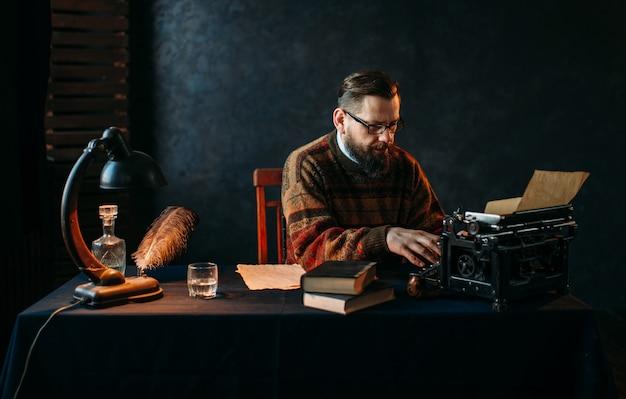 Писатель в очках печатает на старинной пишущей машинке