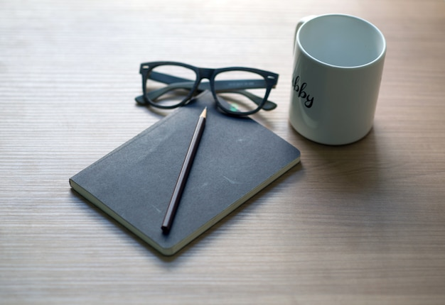 Writer's career on the desk with a white coffee mug, pencil and glasses book