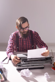 Writers day and technology concept handsome writer surrounded by scraps of paper focused on work